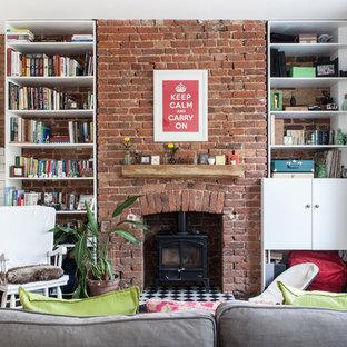 ロンドンのトラディショナルスタイルのおしゃれなLDK (白い壁、薪ストーブ、レンガの暖炉まわり、テレビなし、無垢フローリング) の写真