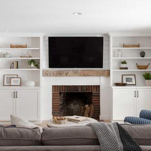 Foto på ett mellanstort lantligt allrum med öppen planlösning, med vita väggar, ljust trägolv, en standard öppen spis, en spiselkrans i tegelsten, en väggmonterad TV och beiget golv