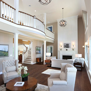 Example of a huge classic formal and open concept medium tone wood floor living room design in Boston with beige walls, a standard fireplace and a wood fireplace surround