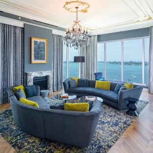 Immagine di un soggiorno design con pareti blu, pavimento in legno massello medio, camino classico e pavimento marrone