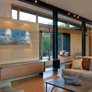 Imagen de salón abierto, minimalista, con paredes beige, suelo de madera clara, chimenea tradicional, marco de chimenea de madera y suelo beige