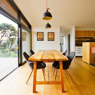 Imagen de salón abierto, pequeño, con paredes blancas, suelo de madera clara, estufa de leña, marco de chimenea de piedra y suelo multicolor