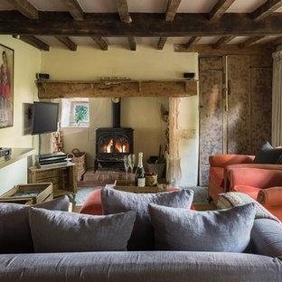 他の地域の中くらいのカントリー風おしゃれな独立型リビング (黄色い壁、カーペット敷き、壁掛け型テレビ、ベージュの床、薪ストーブ) の写真