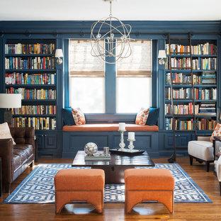 Immagine di un soggiorno classico con libreria, pareti blu, pavimento in legno massello medio e nessuna TV