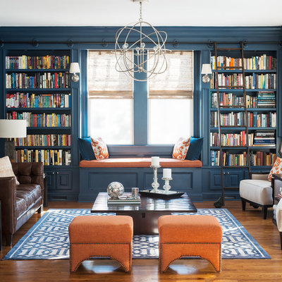 Example of a transitional medium tone wood floor living room library design in New York with blue walls and no tv