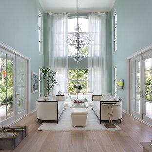 マイアミの巨大なトロピカルスタイルのおしゃれなLDK (フォーマル、青い壁、淡色無垢フローリング、テレビなし) の写真