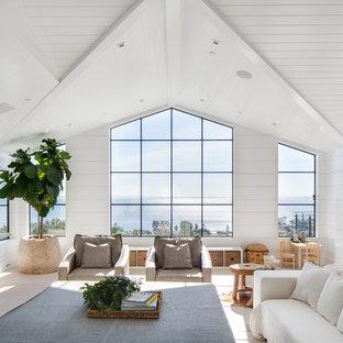 Living room - coastal open concept light wood floor and beige floor living room idea in Orange County with white walls