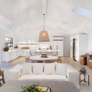 Cette photo montre un grand salon bord de mer ouvert avec un mur blanc, un sol en bois clair, un manteau de cheminée en pierre, une cheminée ribbon, un téléviseur fixé au mur, un sol beige, un plafond voûté, un plafond en bois et du lambris de bois.