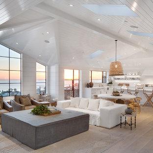 Cette photo montre un grand salon bord de mer ouvert avec un mur blanc et un sol en bois clair.