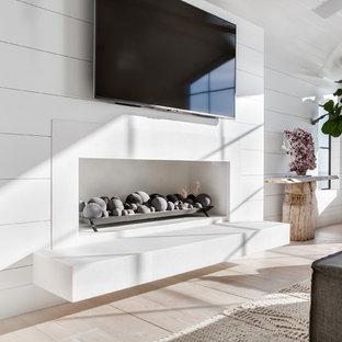 Idéer för ett stort maritimt allrum med öppen planlösning, med vita väggar, ljust trägolv, en bred öppen spis, en spiselkrans i sten, en väggmonterad TV och beiget golv