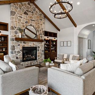 Foto de salón para visitas campestre, sin televisor, con suelo de madera oscura, estufa de leña, marco de chimenea de piedra y paredes grises