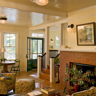Living room - traditional living room idea in Portland Maine with yellow walls, a standard fireplace and a brick fireplace