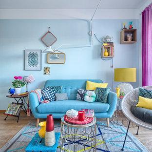 Foto de salón para visitas cerrado, ecléctico, de tamaño medio, sin chimenea y televisor, con paredes azules y suelo de madera clara