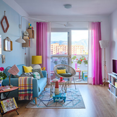 Inspiration for a mid-sized eclectic formal and enclosed light wood floor living room remodel in Malaga with blue walls and a tv stand