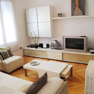 This is an example of a small contemporary formal enclosed living room in Madrid with white walls, medium hardwood flooring, no fireplace and a freestanding tv.