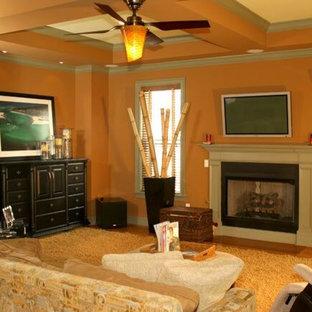アトランタの中サイズのトランジショナルスタイルのおしゃれなLDK (オレンジの壁、淡色無垢フローリング、標準型暖炉、コンクリートの暖炉まわり、据え置き型テレビ) の写真