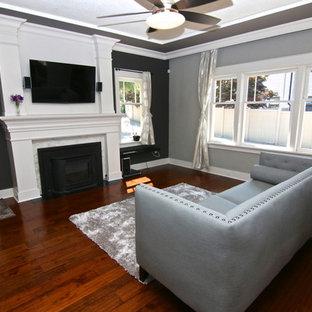 Esempio di un piccolo soggiorno stile americano chiuso con pareti grigie, parquet scuro, stufa a legna, cornice del camino in legno e TV a parete