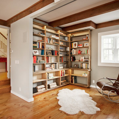 Example of a farmhouse medium tone wood floor living room library design in New York with gray walls