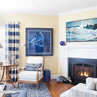 ボストンの中サイズのビーチスタイルのおしゃれなLDK (フォーマル、黄色い壁、無垢フローリング、コーナー設置型暖炉、木材の暖炉まわり、テレビなし、茶色い床) の写真