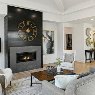 ミネアポリスの中くらいのトランジショナルスタイルのおしゃれなLDK (フォーマル、白い壁、淡色無垢フローリング、横長型暖炉、塗装板張りの暖炉まわり、壁掛け型テレビ、茶色い床) の写真