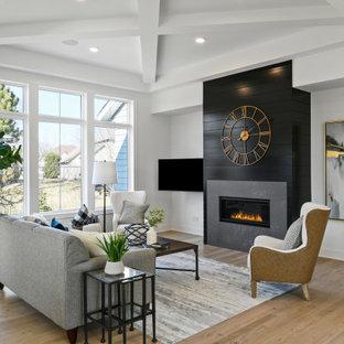 Repräsentatives, Offenes, Großes Klassisches Wohnzimmer mit weißer Wandfarbe, hellem Holzboden, Gaskamin, Kaminumrandung aus Holzdielen, Wand-TV und braunem Boden in Minneapolis