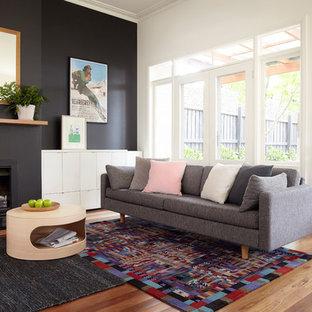 Modernes Wohnzimmer mit schwarzer Wandfarbe, braunem Holzboden und Kamin in Melbourne