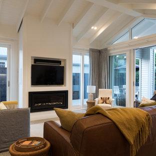 Esempio di un soggiorno design di medie dimensioni e chiuso con libreria, pareti multicolore, pavimento in cemento, camino sospeso, cornice del camino in legno, TV a parete e pavimento grigio