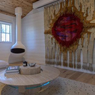 Foto di un soggiorno stile marino aperto con pareti bianche, parquet chiaro, camino sospeso, TV nascosta e pavimento beige