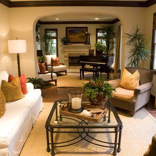 Immagine di un piccolo soggiorno chic chiuso con sala della musica, pareti beige, pavimento in terracotta, camino classico, cornice del camino in cemento e nessuna TV