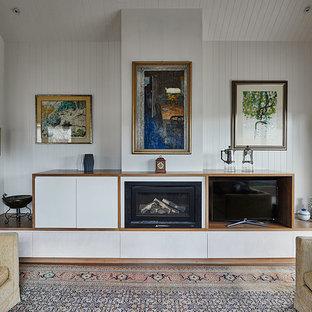 ジーロングの中サイズのビーチスタイルのおしゃれなリビング (白い壁、淡色無垢フローリング、標準型暖炉、木材の暖炉まわり、据え置き型テレビ、茶色い床) の写真