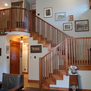 Cette image montre un salon mansardé ou avec mezzanine craftsman de taille moyenne avec un mur beige, un sol en bois brun, une cheminée standard, un manteau de cheminée en pierre, un téléviseur indépendant et un sol marron.