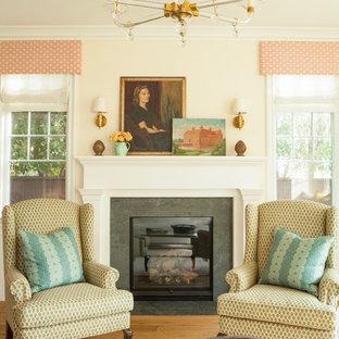 Ejemplo de salón para visitas cerrado, campestre, grande, con paredes amarillas, suelo de madera clara, chimenea tradicional, marco de chimenea de piedra y suelo marrón