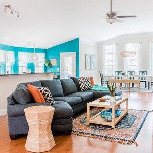 Aménagement d'un salon bord de mer de taille moyenne et ouvert avec un mur beige, un sol en bois brun, aucune cheminée, un téléviseur indépendant et un sol marron.