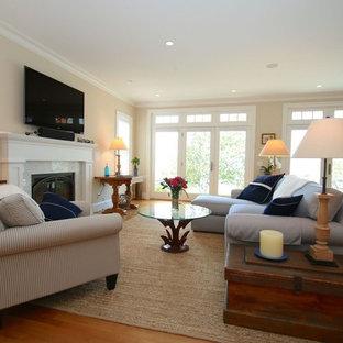 ニューヨークの大きいビーチスタイルのおしゃれなLDK (フォーマル、黄色い壁、無垢フローリング、標準型暖炉、石材の暖炉まわり、据え置き型テレビ、茶色い床) の写真