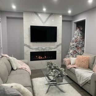 Modelo de salón moderno con paredes grises, suelo de madera en tonos medios, chimenea tradicional, marco de chimenea de baldosas y/o azulejos y suelo turquesa