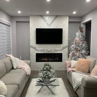 Imagen de salón minimalista con paredes grises, suelo de madera en tonos medios, chimenea tradicional, marco de chimenea de baldosas y/o azulejos y suelo turquesa