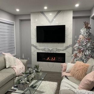 Diseño de salón moderno con paredes grises, suelo de madera en tonos medios, chimenea tradicional, marco de chimenea de baldosas y/o azulejos y suelo turquesa