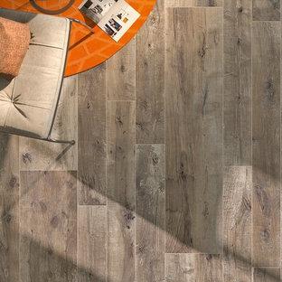 Immagine di un grande soggiorno american style aperto con libreria, cornice del camino piastrellata e pavimento in gres porcellanato