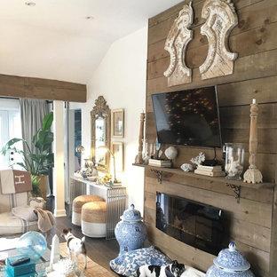 トロントの小さいビーチスタイルのおしゃれなLDK (ベージュの壁、濃色無垢フローリング、吊り下げ式暖炉、木材の暖炉まわり、壁掛け型テレビ、茶色い床) の写真