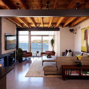 Diseño de salón cerrado, moderno, grande, con suelo de cemento, paredes marrones, chimenea tradicional y televisor colgado en la pared