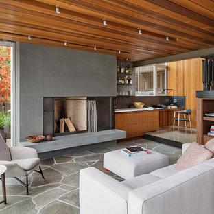 Bild på ett funkis allrum med öppen planlösning, med skiffergolv, en standard öppen spis, en hemmabar och en spiselkrans i betong