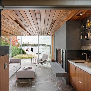 Immagine di un soggiorno minimalista con angolo bar, pavimento in ardesia, camino classico, cornice del camino in pietra e TV nascosta