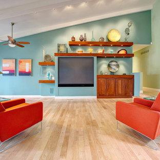 Foto de salón abierto, actual, de tamaño medio, sin chimenea, con paredes azules, suelo de madera clara, pared multimedia y suelo beige