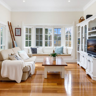 Design ideas for a traditional living room in Sydney with beige walls, medium hardwood floors, a built-in media wall and brown floor.