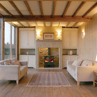 Foto de salón para visitas escandinavo con paredes beige, suelo de madera clara y estufa de leña