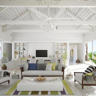 Exemple d'un grand salon exotique fermé avec un mur blanc, un sol en bois peint, un téléviseur fixé au mur, un sol blanc et une salle de réception.
