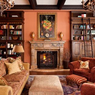 トロントのトラディショナルスタイルのおしゃれなリビング (ライブラリー、オレンジの壁、標準型暖炉) の写真