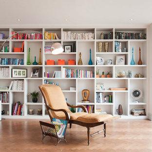 Cette image montre un salon avec une bibliothèque ou un coin lecture design ouvert avec un sol en bois clair.