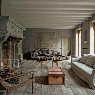 Réalisation d'un très grand salon style shabby chic ouvert avec un mur gris, un sol en bois brun, une cheminée standard, un manteau de cheminée en pierre et aucun téléviseur.