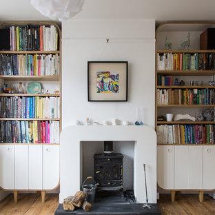 Idee per un soggiorno classico di medie dimensioni e chiuso con libreria, pareti bianche, pavimento in legno massello medio, stufa a legna e cornice del camino in intonaco